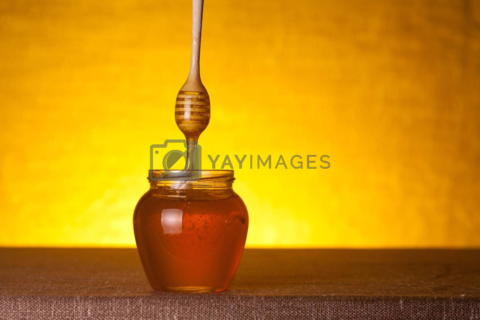 Honey jar with wooden dipper and flowing honey, studio shot over yellow background
