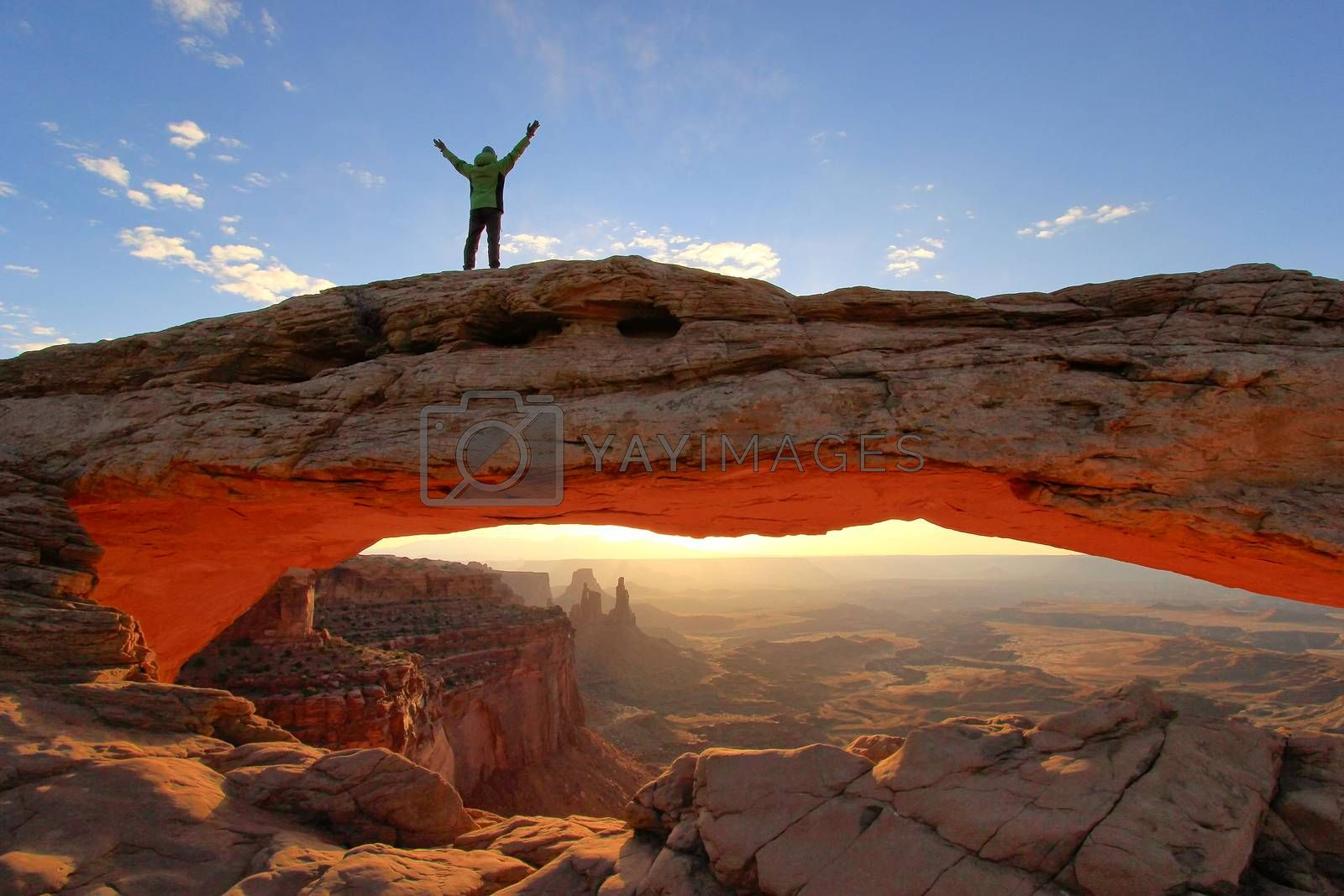 Royalty free image of Silhouetted person standing on top of Mesa Arch, Canyonlands Nat by donya_nedomam