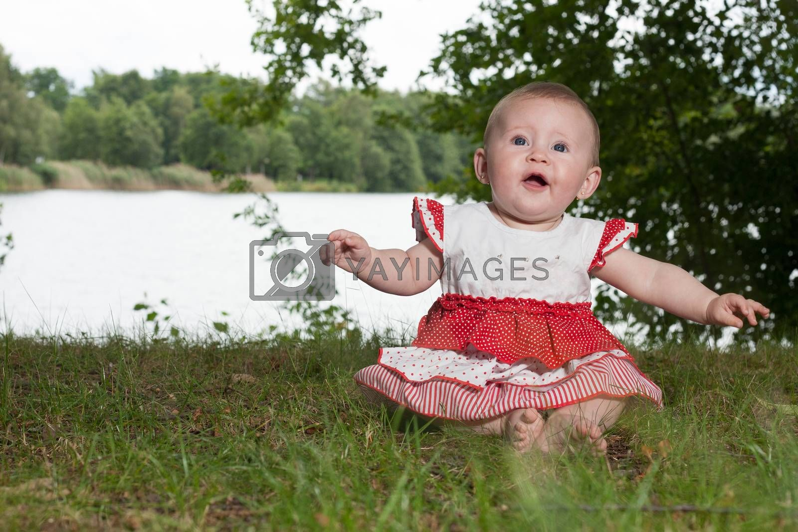 Little baby girl is sitting and playing near the lake