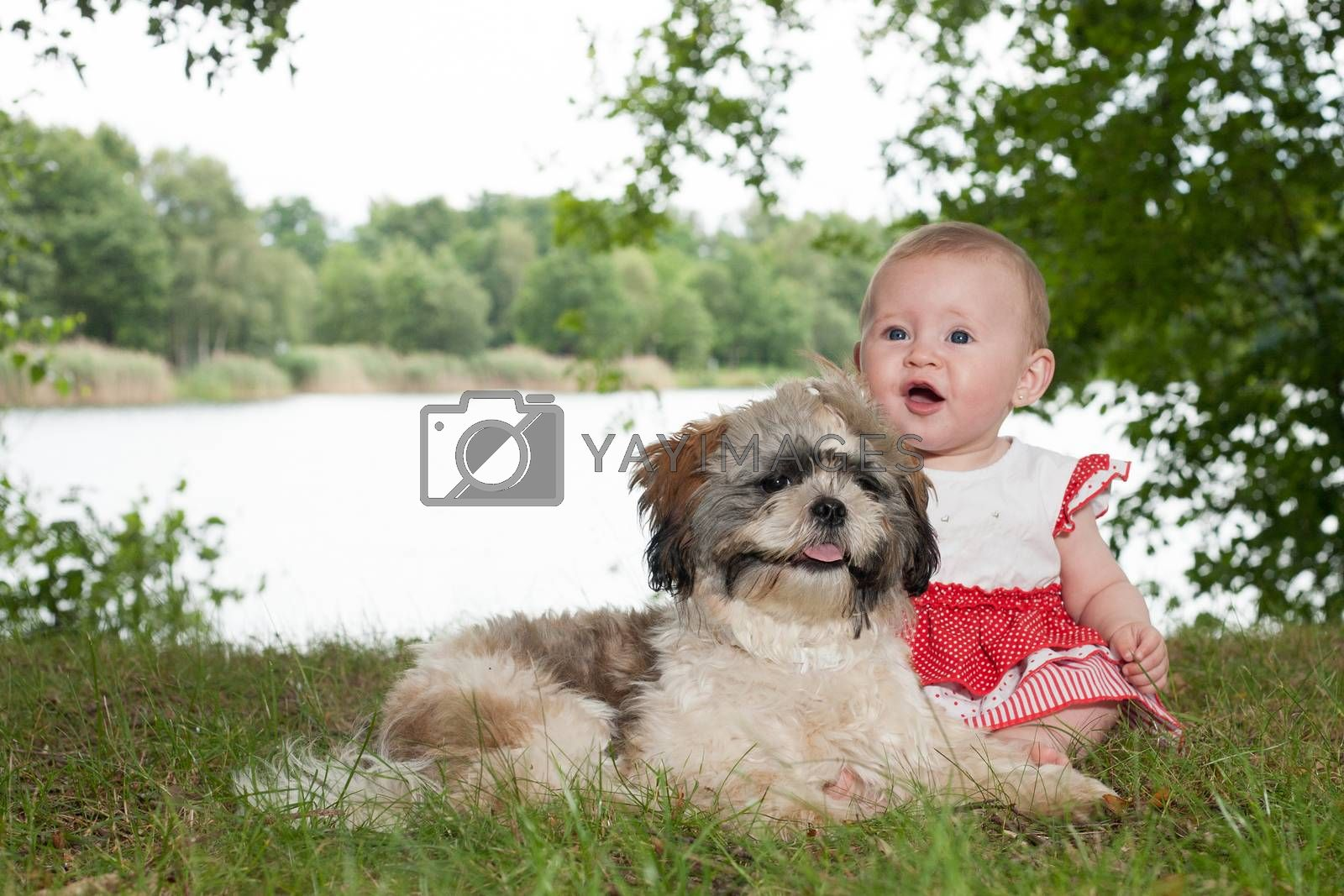 Baby and puppy are playing near the lake