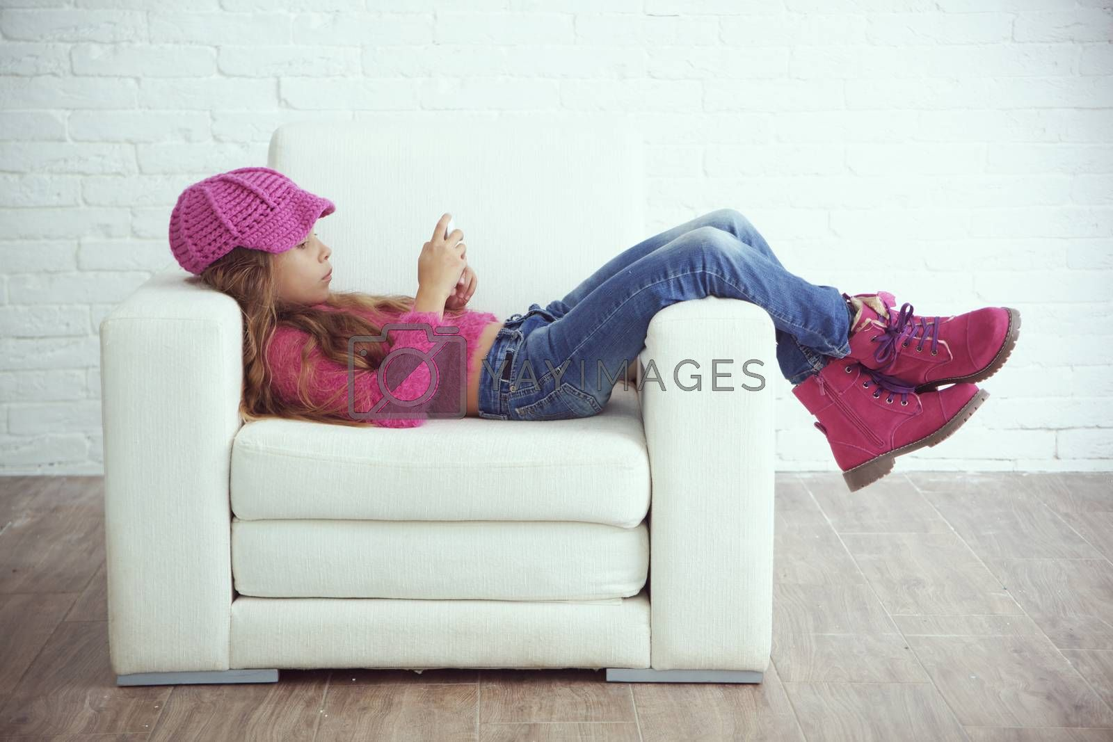 Cute pre-teen girl wearing fashion winter clothes posing in white interior