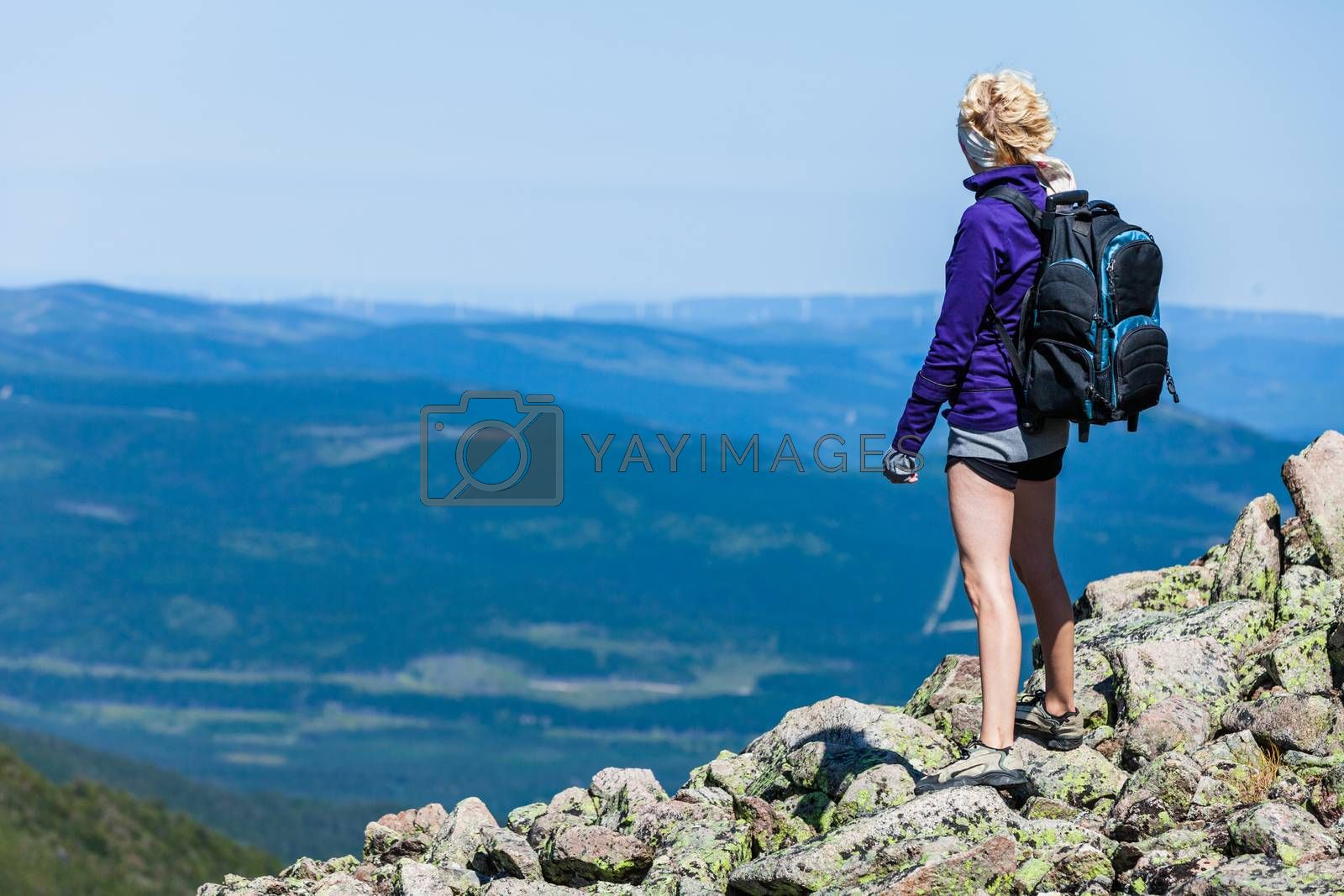Young Woman with Backpack Looking at the View From the Top of the Hill