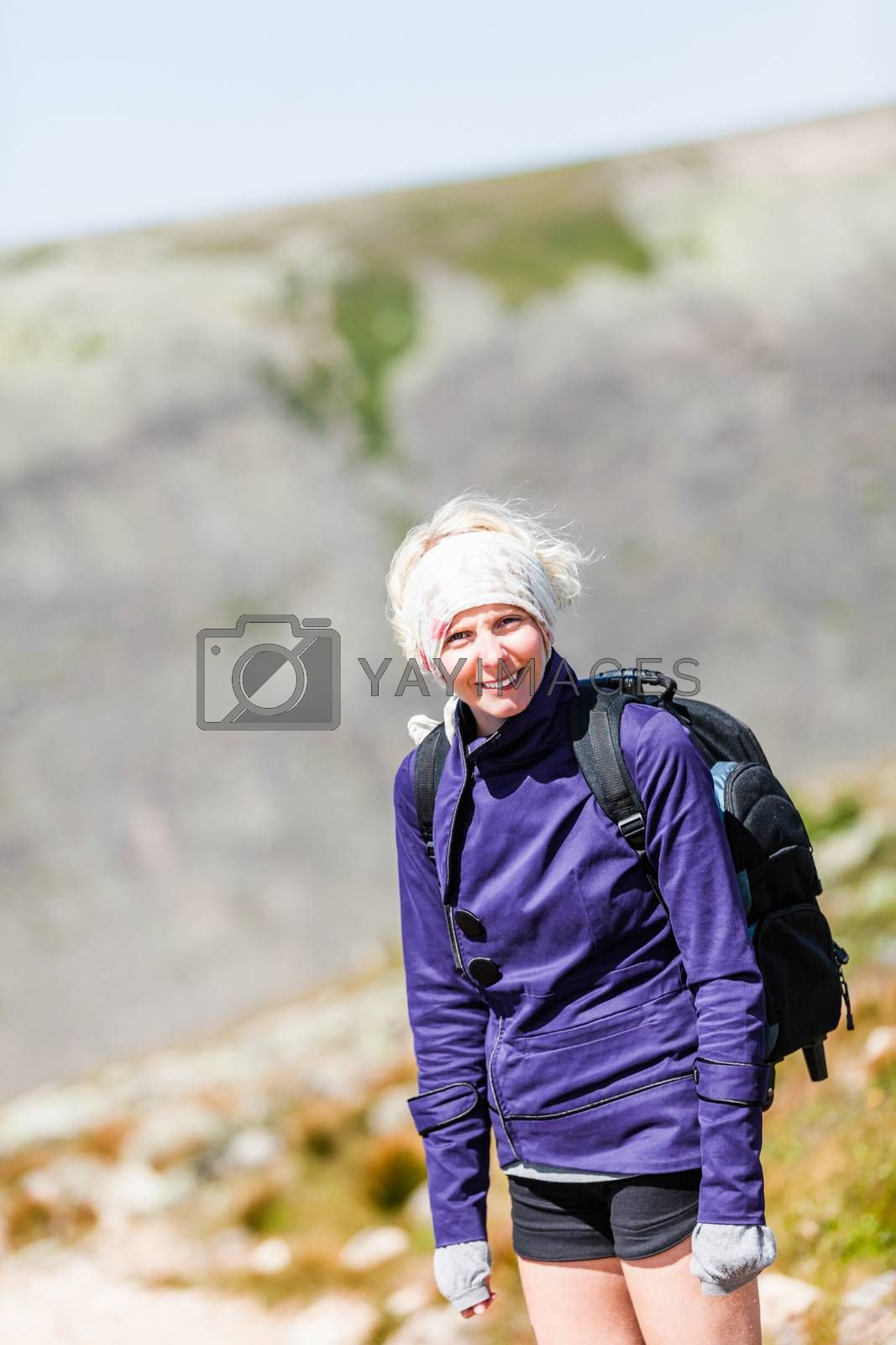 Young Woman Walking on a Rocky Hiking Path and looking at the camera