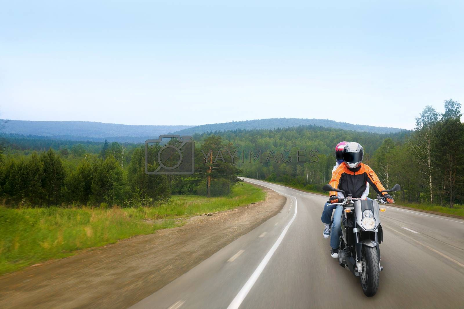 motorcyclist and passenger go on country road