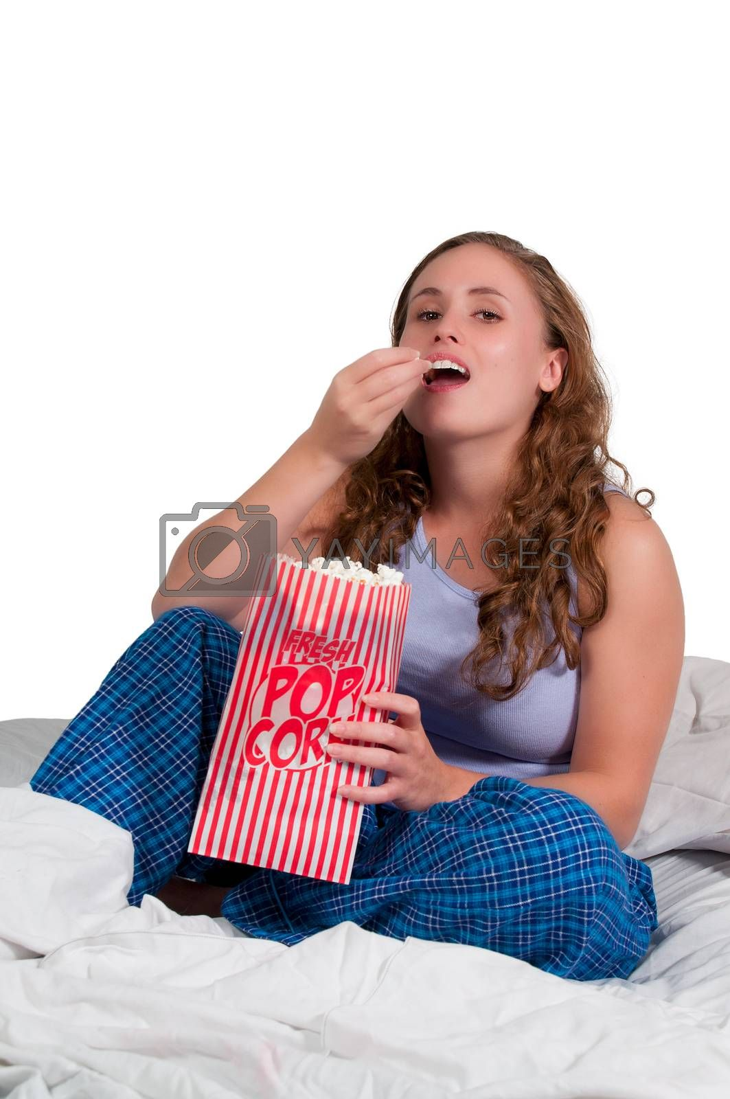 Beautiful young woman eating popcorn in bed