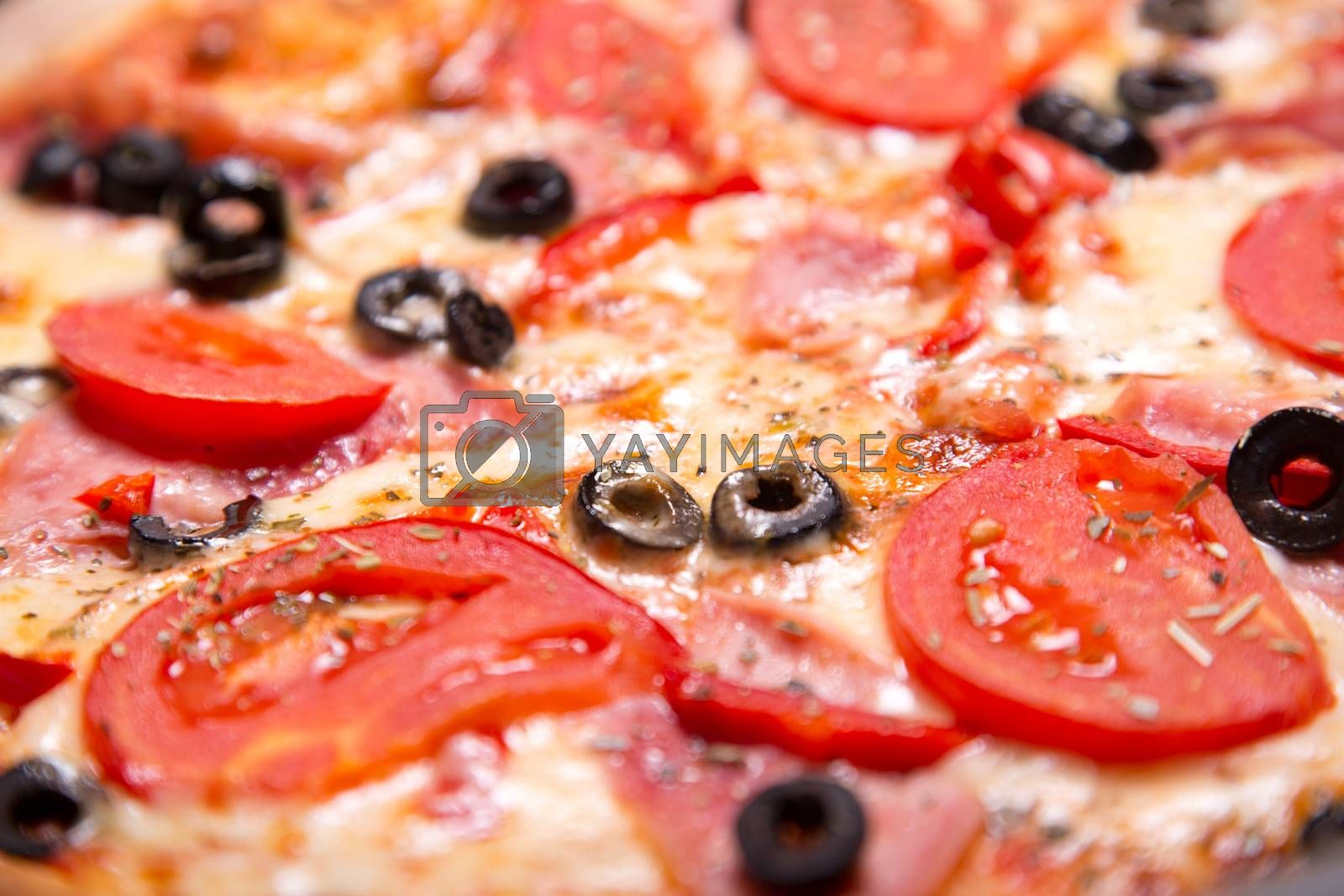 Close-up shot of delicious Italian pizza with ham, tomatoes and olives, selective focus