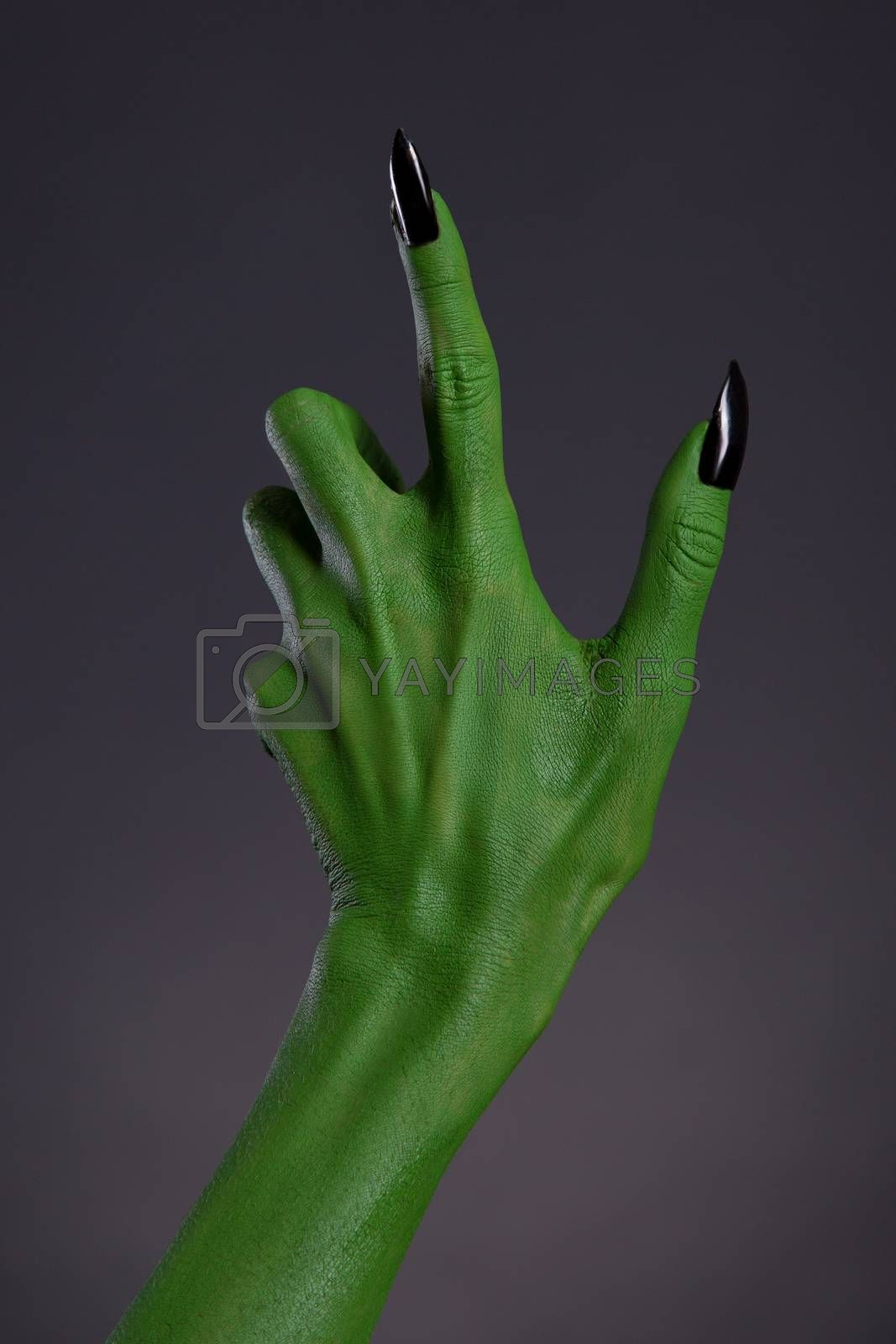 Green witch hand with black nails, Halloween theme, studio shot on black background