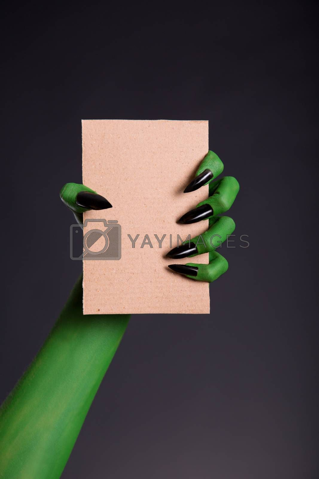 Green monster hand with black nails holding blank piece of cardboard, Halloween theme