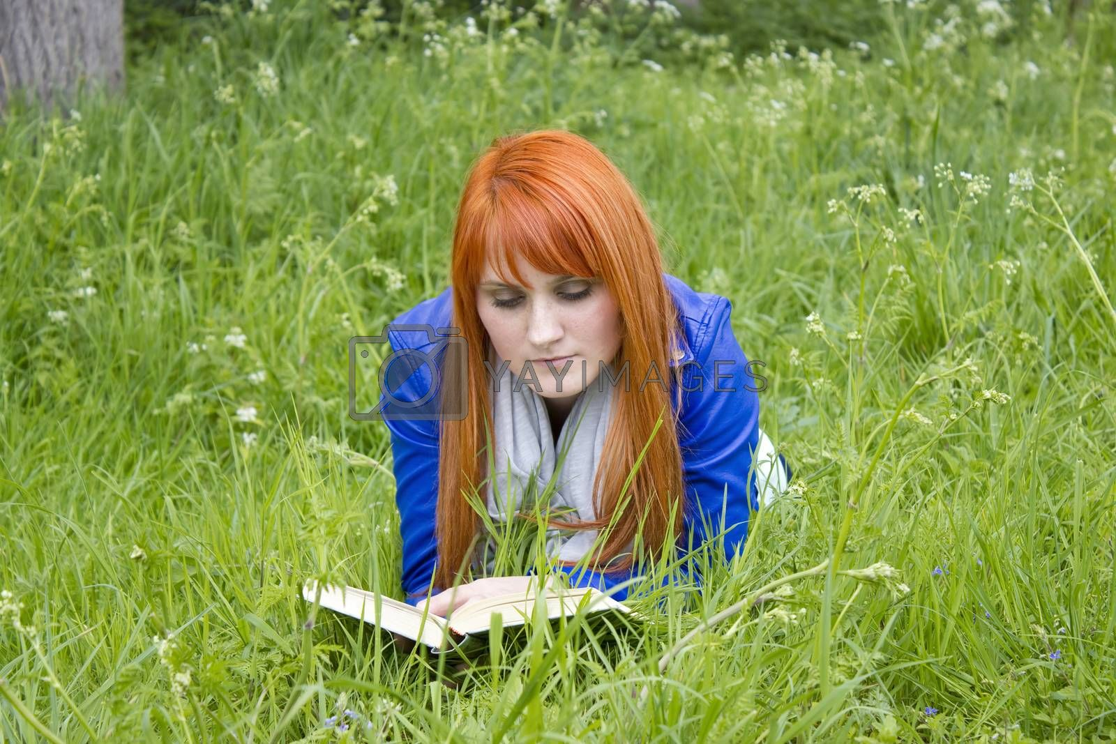 Royalty free image of Young woman with red hair reading a book  by miradrozdowski