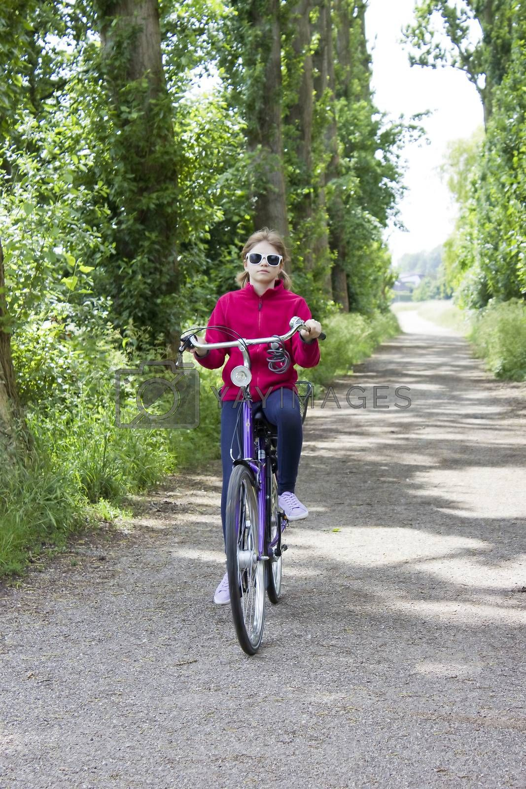 Royalty free image of young girl with her bicycle by miradrozdowski