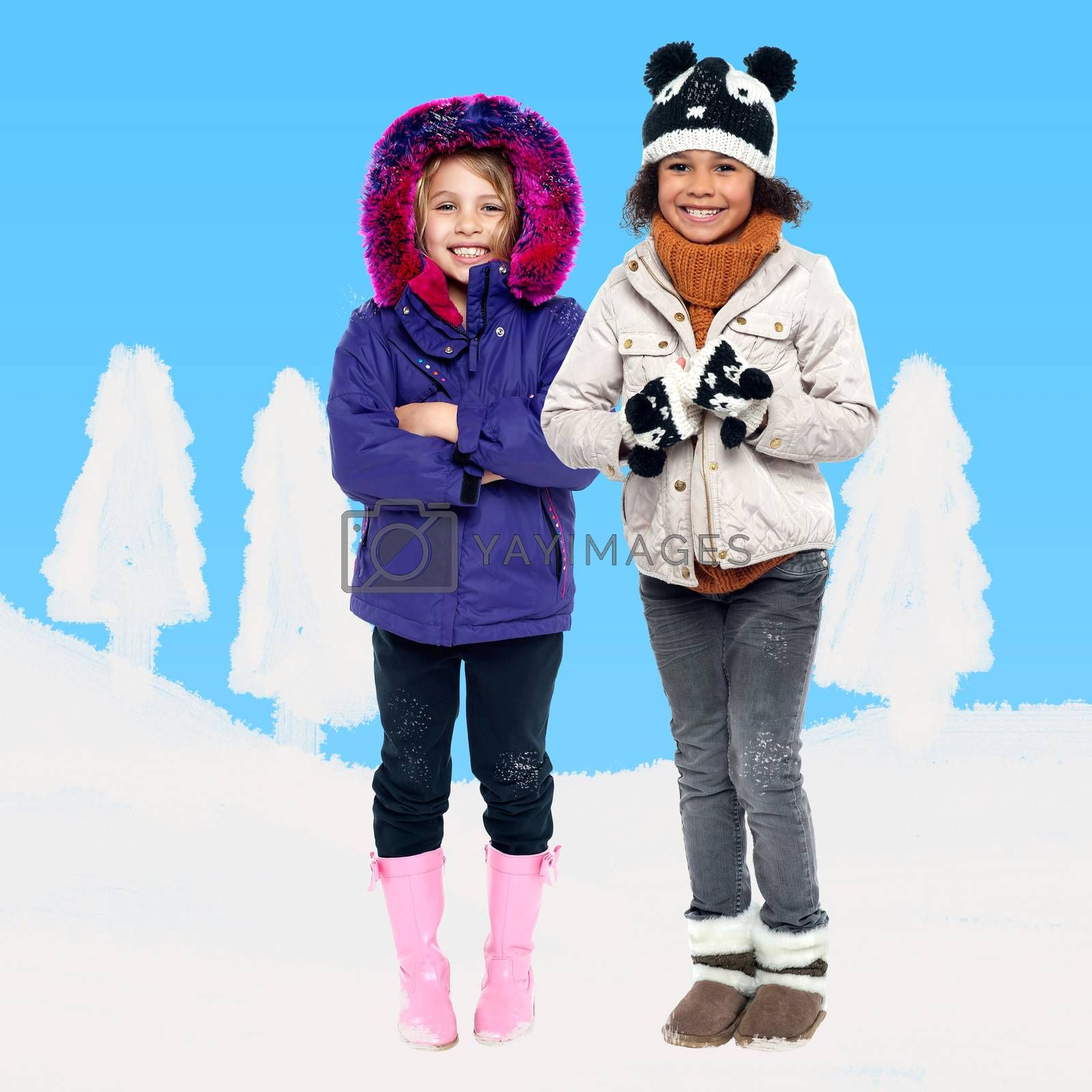 Two kids in winter wear against snow background