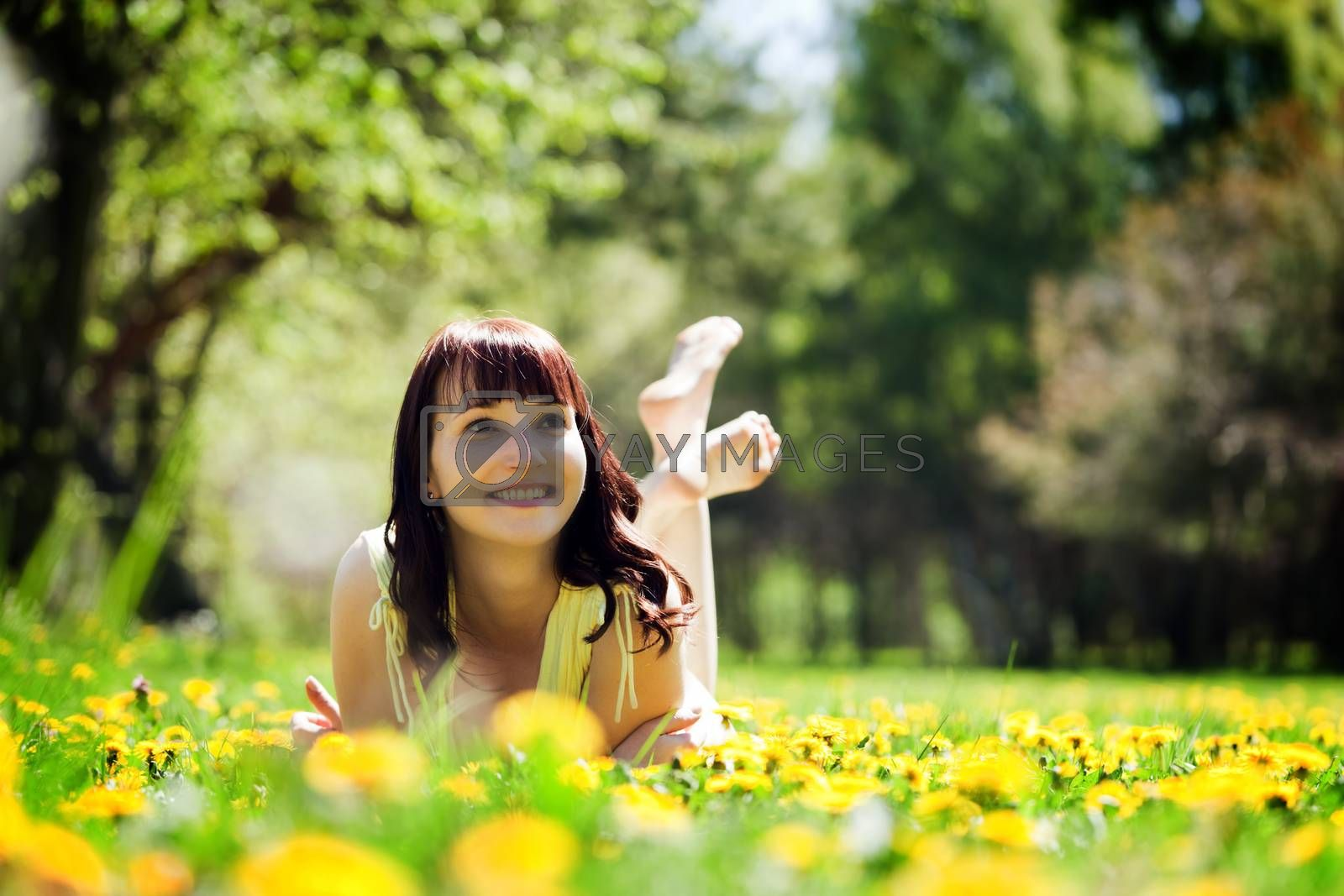 Royalty free image of Young beautiful woman lying on grass full of spring flowers and smiling. by photocreo