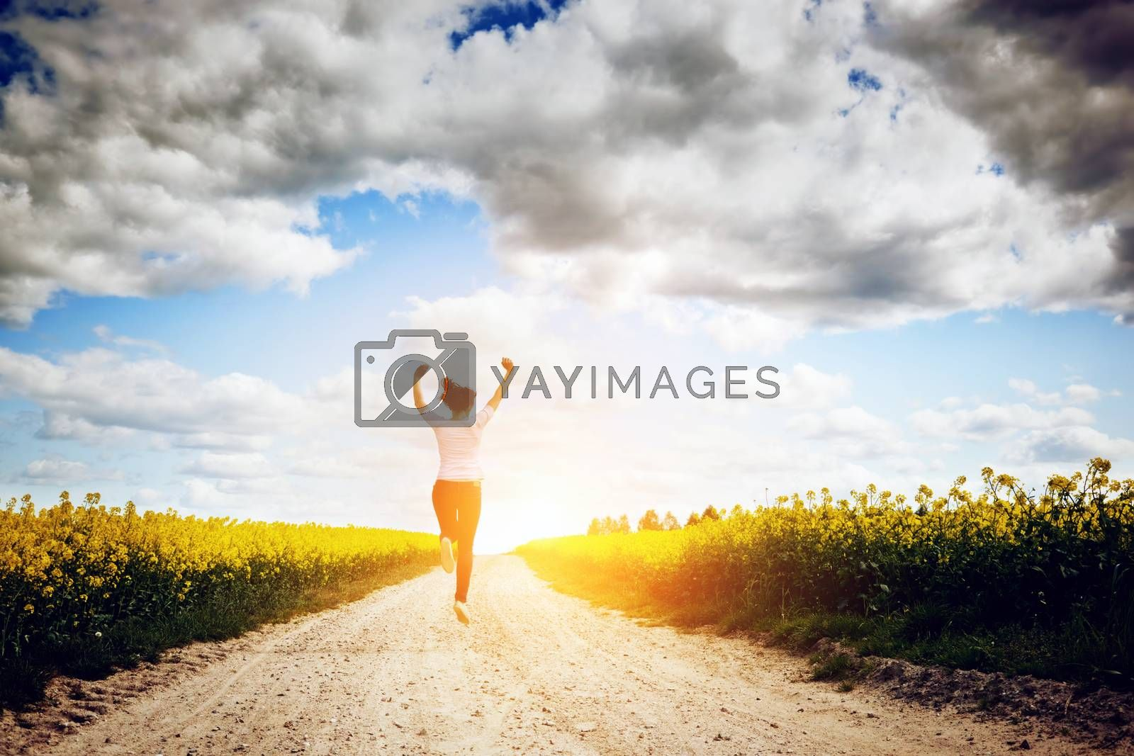 Royalty free image of Happy young woman running and jumping for joy towards sun by photocreo