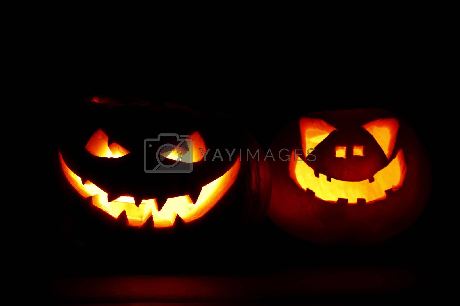 Two carved Halloween pumpkins jack-o-lantern on dark background