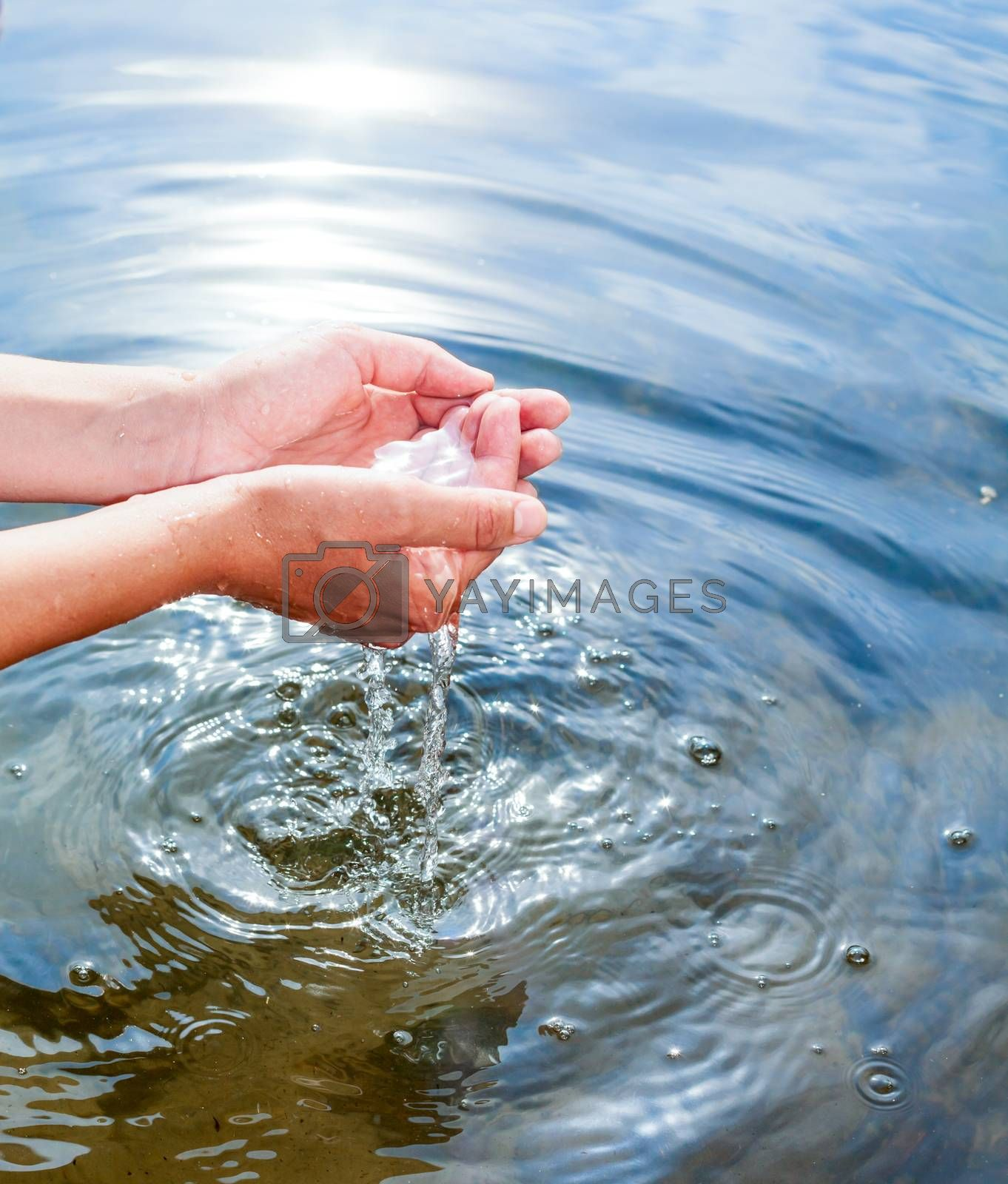 Woman taking clear water at a lake by hands