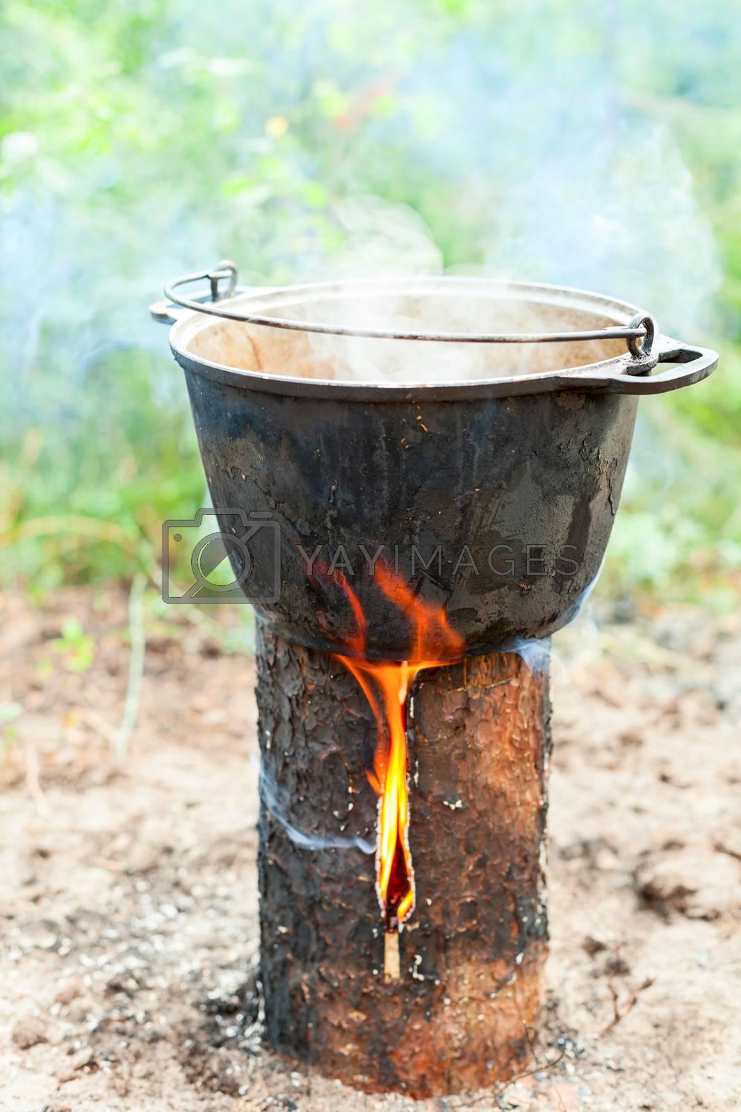 Cooking Goulash soup in cauldron on Finnish (Swedish) log stove