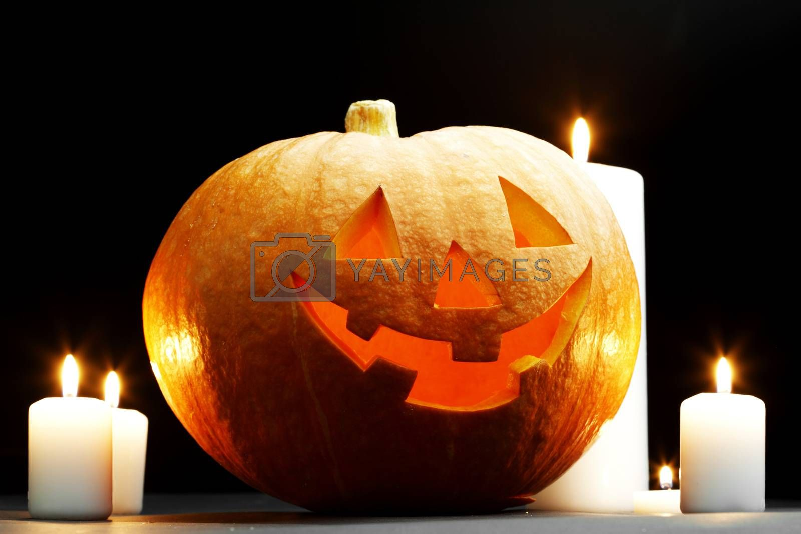 Halloween pumpkin surrounded with candles isolated on black background
