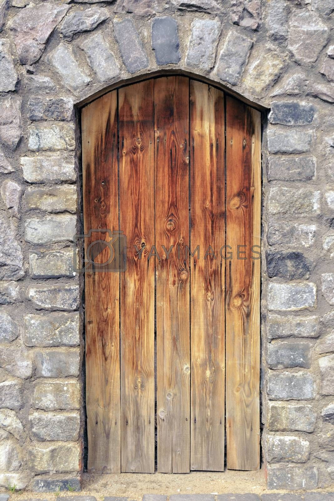 old time wooden door in medieval stone wall