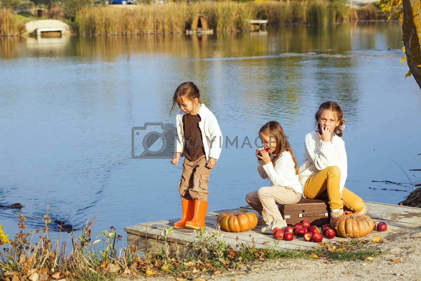 Three cheerful little girls playing on the lake in warm autumn day / Fall lifestyle portrait of children having fun on wooden bearth over the river landscape