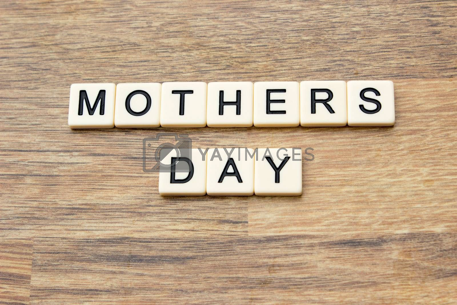 The word mothers day written in tiles on a wooden surface