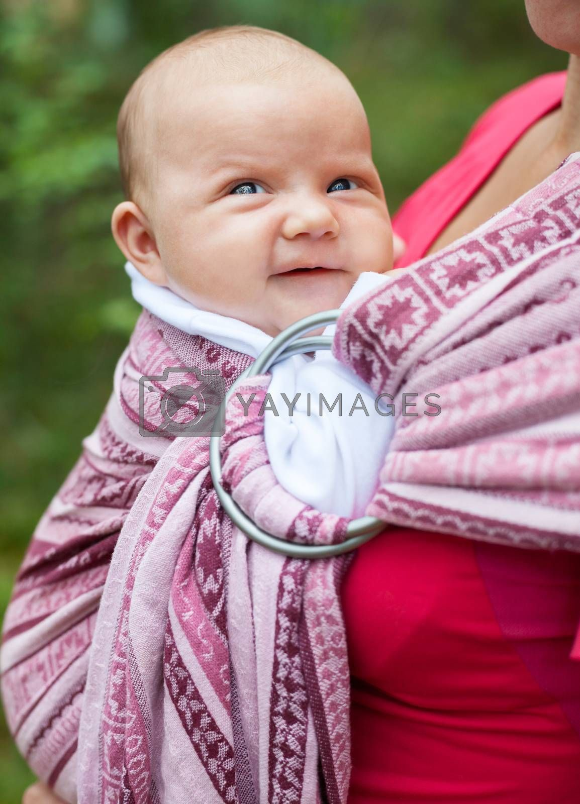 Mother carrying her child in a baby sling