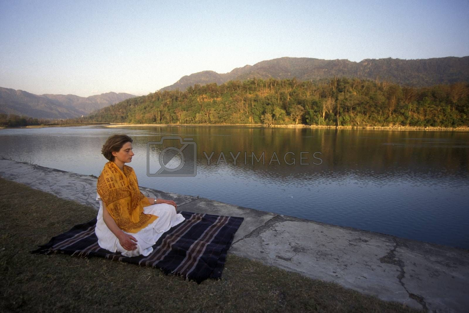 a women on the Ganges River in the town of Rishikesh in the Province Uttar Pradesh in India.