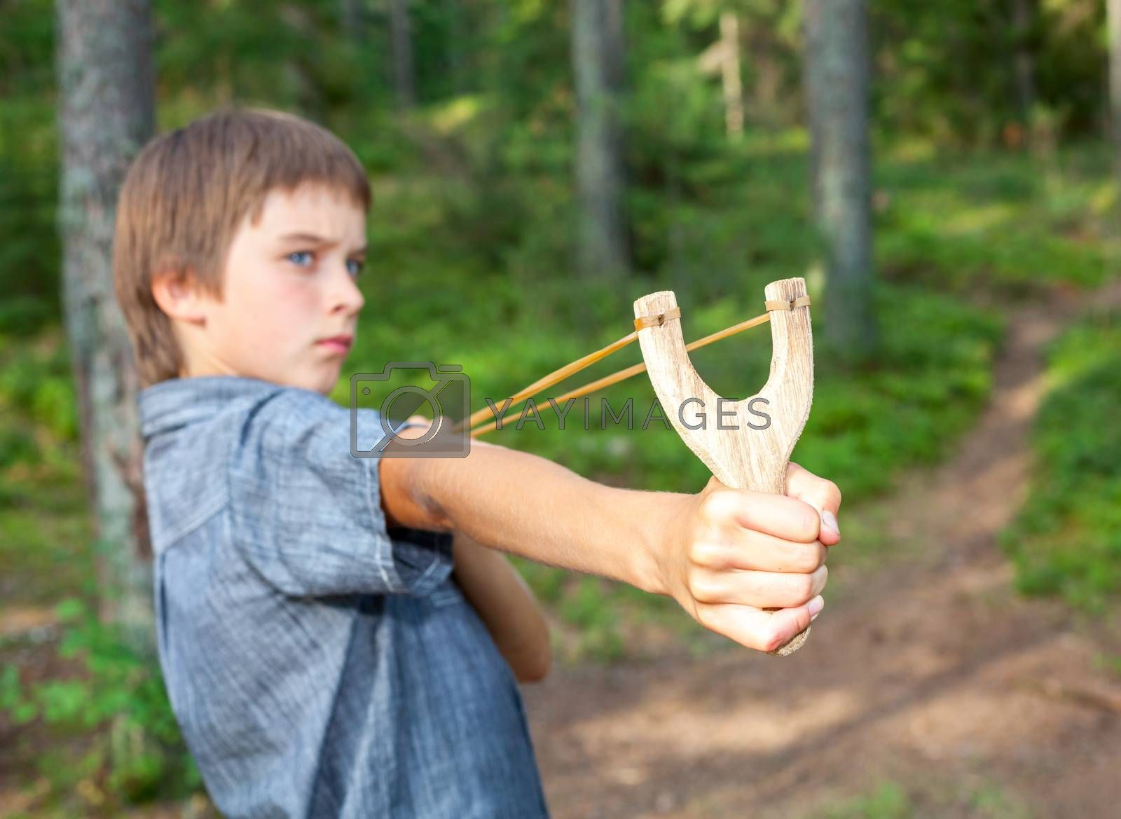 Boy aiming wooden slingshot outdoors