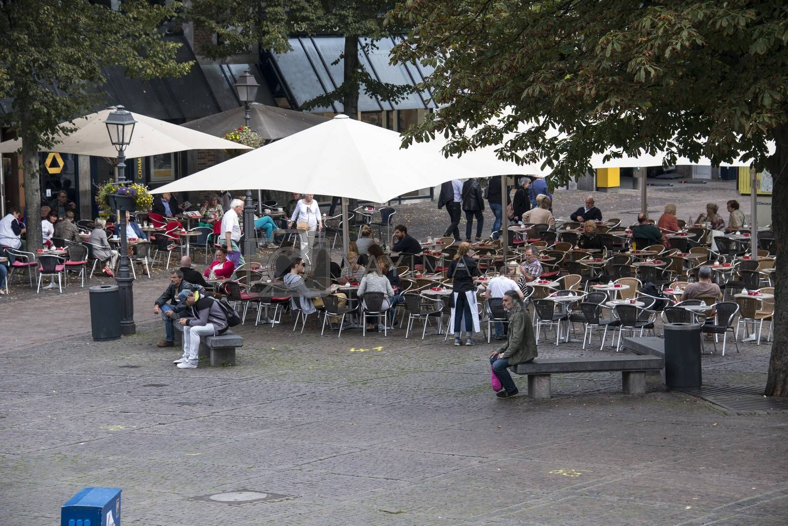 GERMANY,AACHEN - SEPT 29; 2014: Tourists Having Lunch At Outdoor Restaurant in the center of Aachen,Aachen is famous because of the dom church next to this terrace