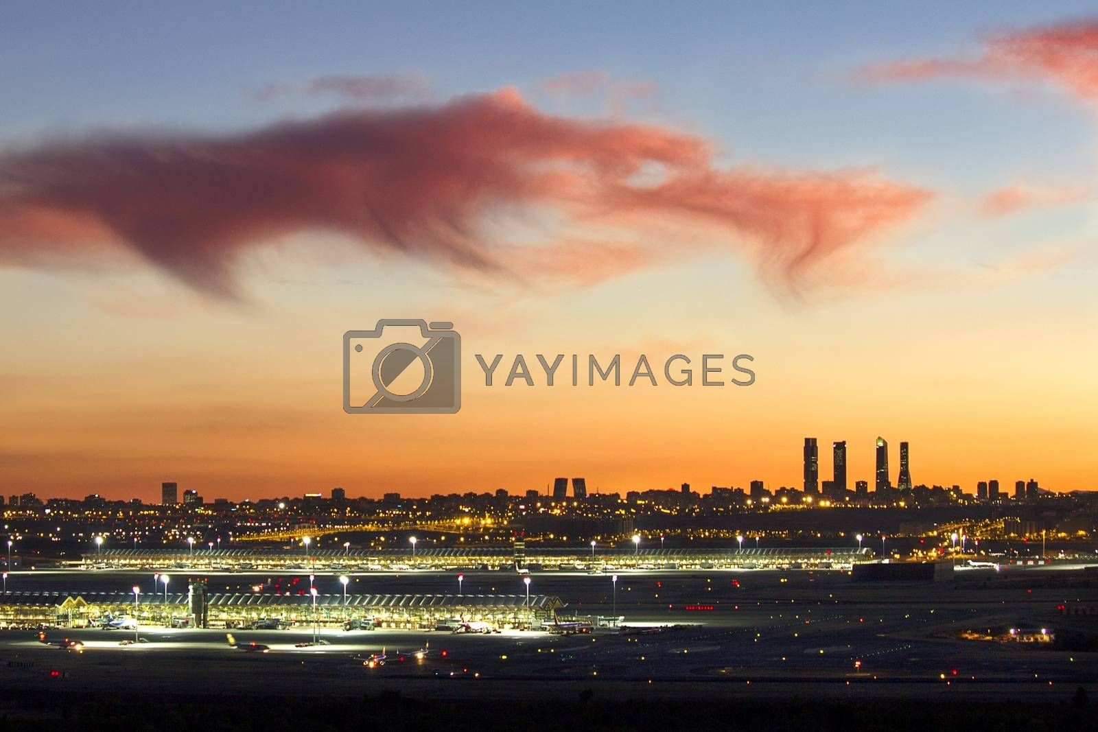 This is a view of Madrid from the Airport at sunset, with the lights of the city and the beautiful orange and blue cloudy sky.