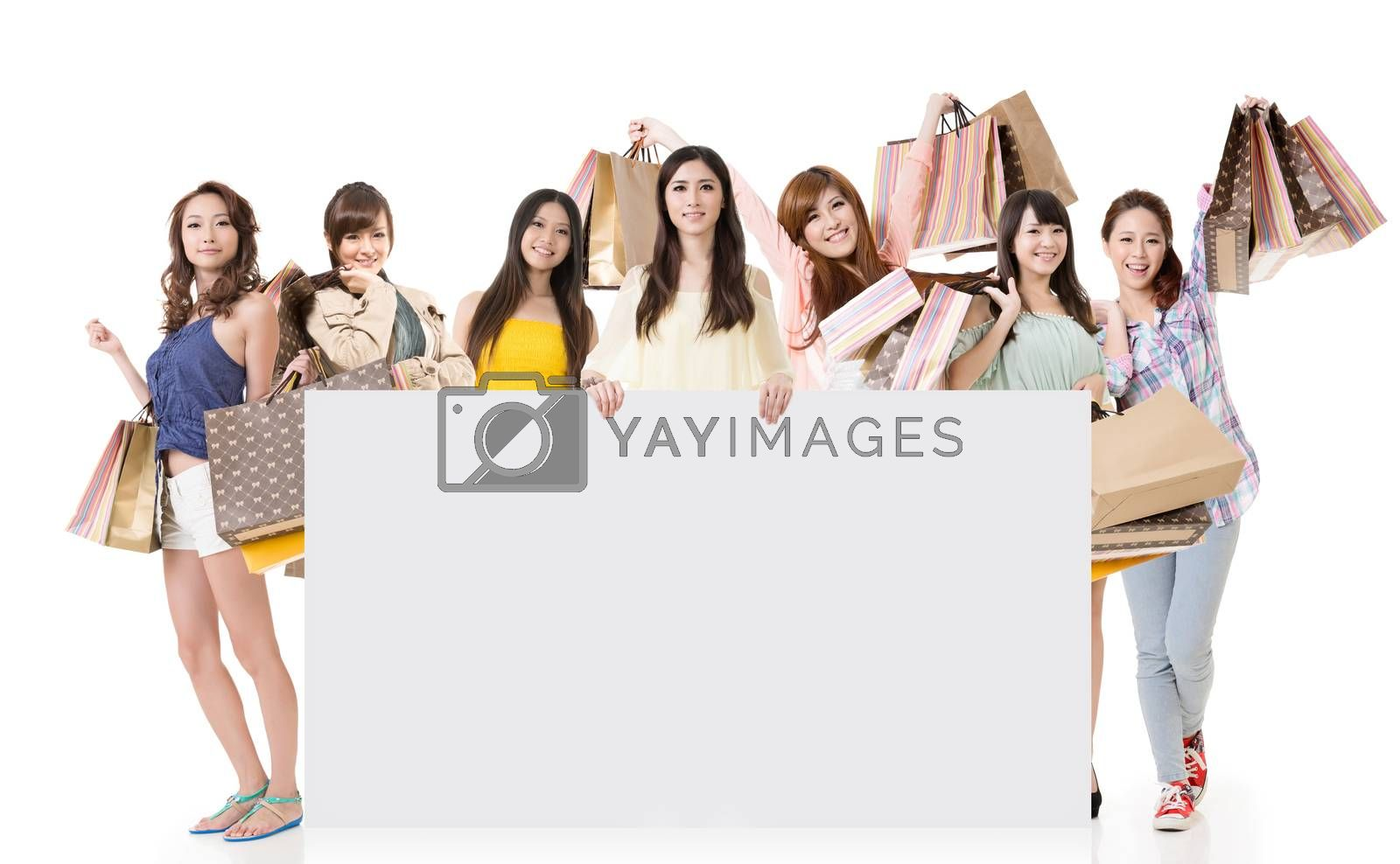 Attractive Asian woman shopping and one lady holding blank board, full length portrait isolated on white background.