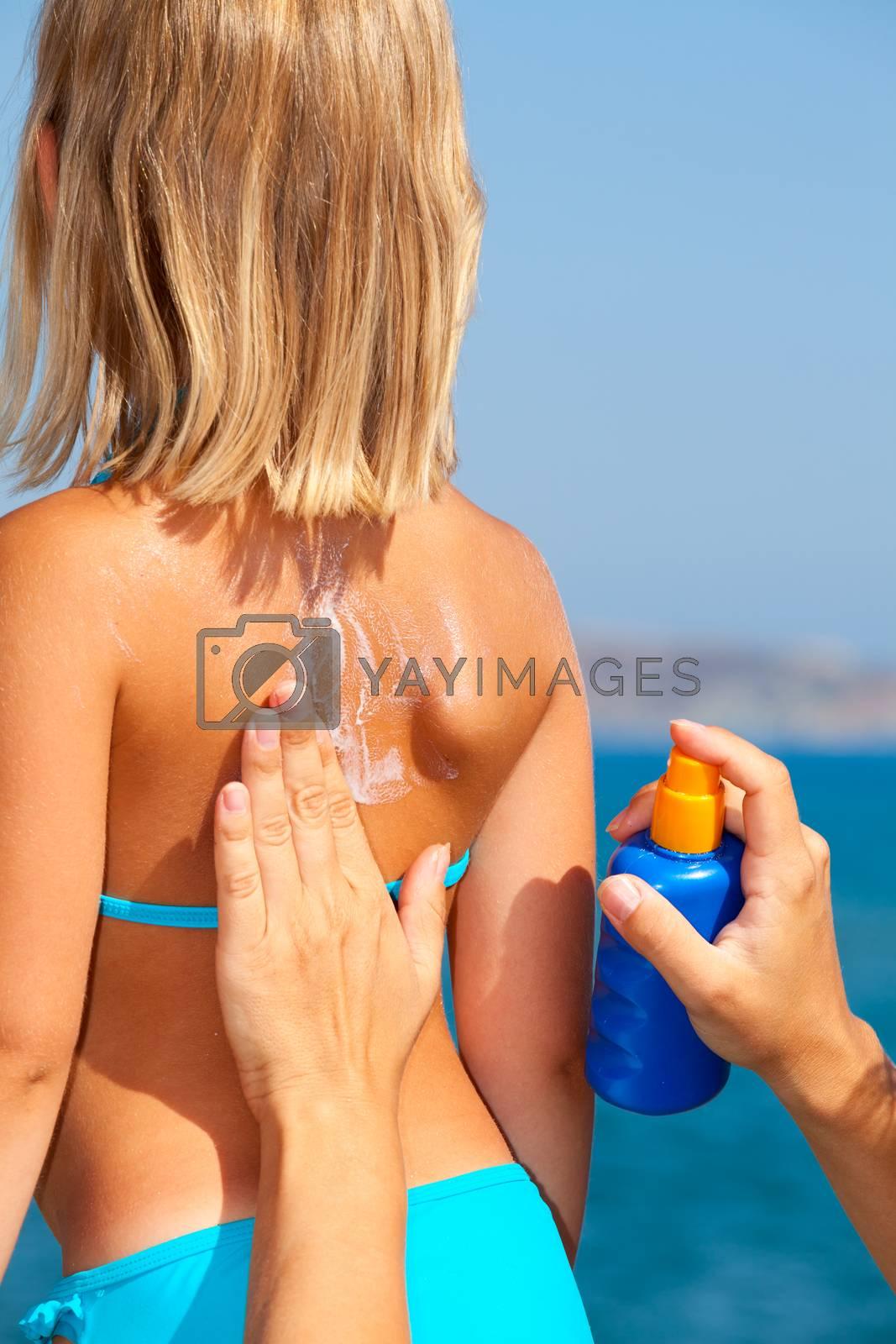 Mother applys sunblock cream on daughter's back