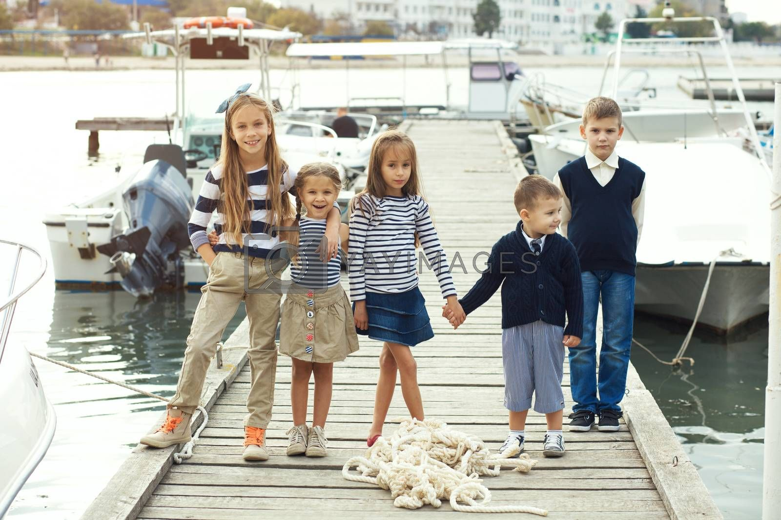 Many fashion kids wearing navy clothes in marine style walking in the sea port and holding hands