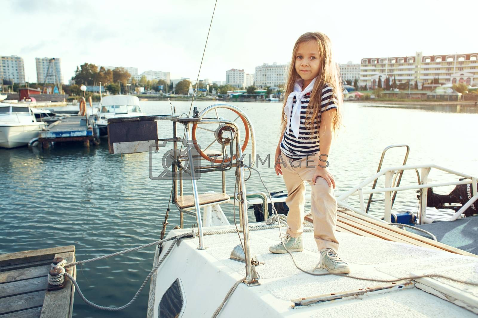 Fashion child wearing navy clothes in marine style posing on white yacht in sea port
