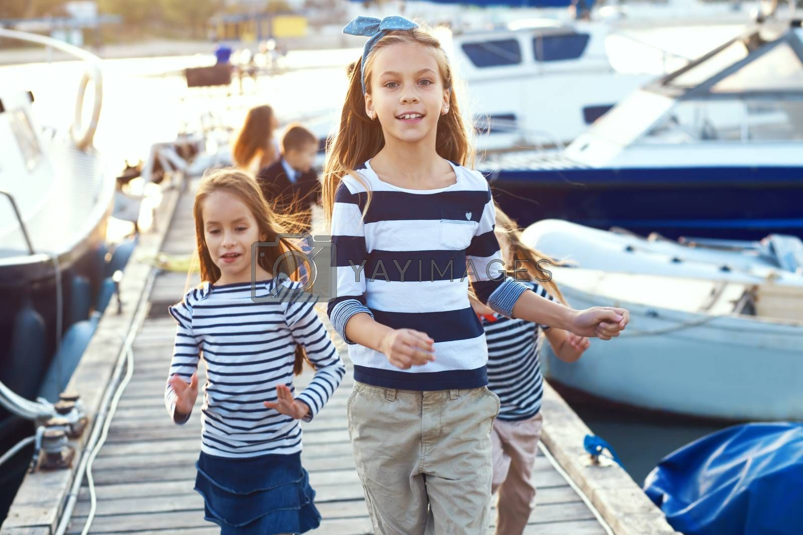 Group of fashion children wearing striped navy clothes in marine style walking in the sea port