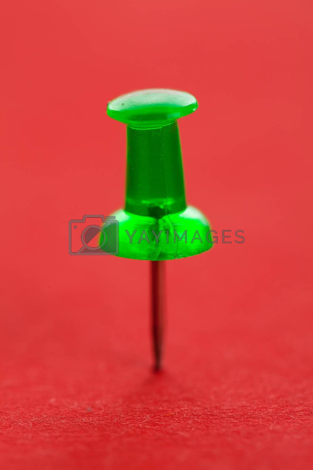 Green pushpin on a red surface