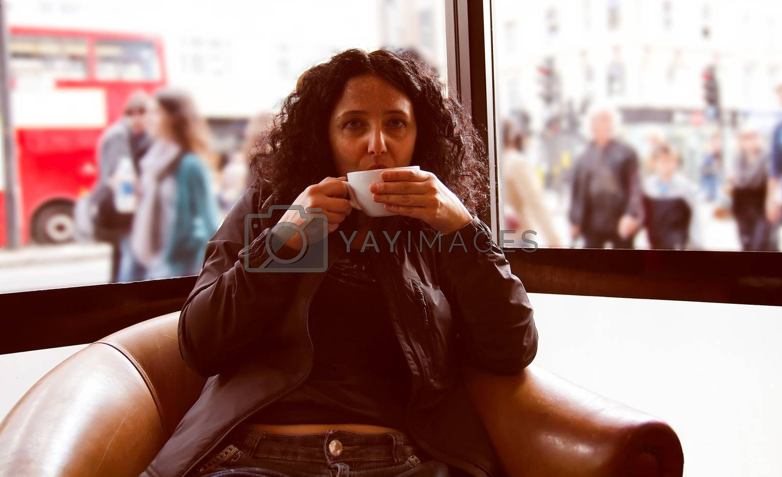 A pretty young brunette girl woman female drinking a cup of coffee or tea
