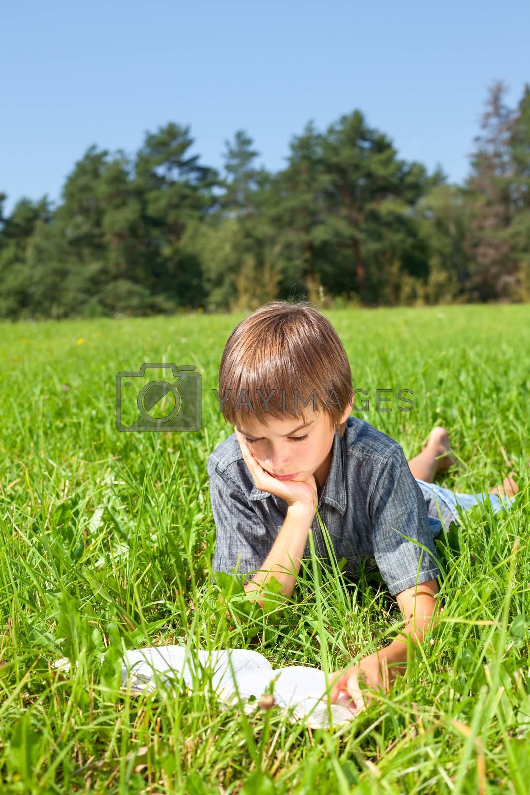 Boy lying in grass reading a book in a summer field