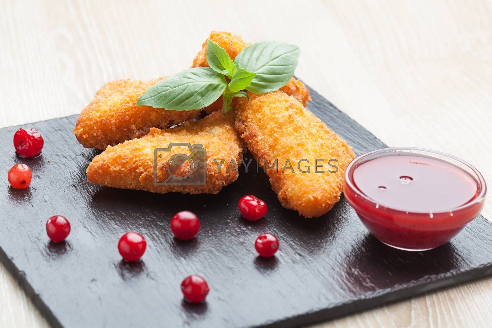 Appetizer fried cheese sticks served with basil, cranberries, and red berry sauce in bowl on black stone plate