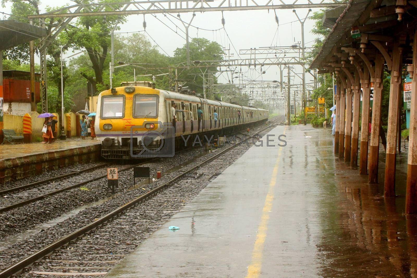 An Indian local train leaves a rural station during heavy monsoon rains season