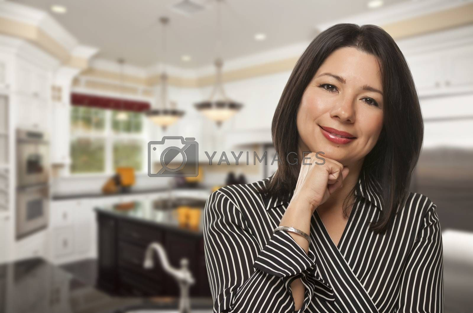 Attractive Hispanic Woman Standing in Beautiful Custom Kitchen.