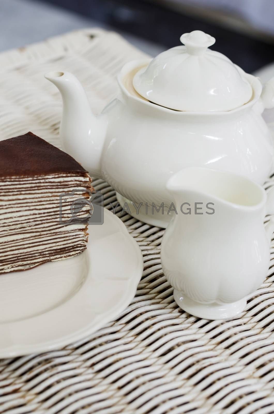 Teapot with chocolate crape cake on weave texture table