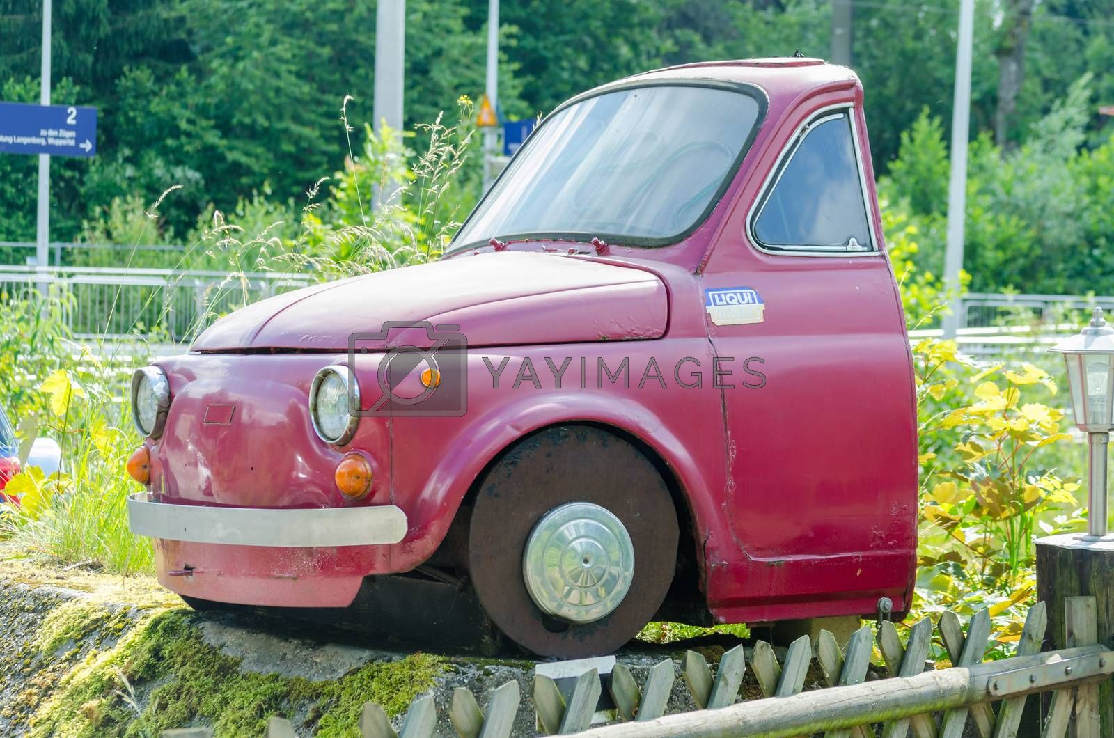 Essen, Nrw, Germany - June 13, 2014: Velber Langenberg district is that half red Fiat 500 car behind the front seats separated. By overgrown grass. Fiat SpA is an Italian automobile manufacturer, engine manufacturer, financial and industrial group based in Turin in the Piedmont region.