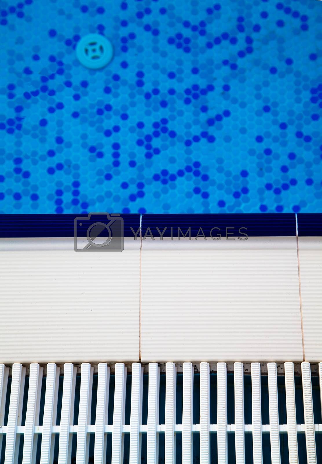 Close up view of tiles of swimming pool with blue water