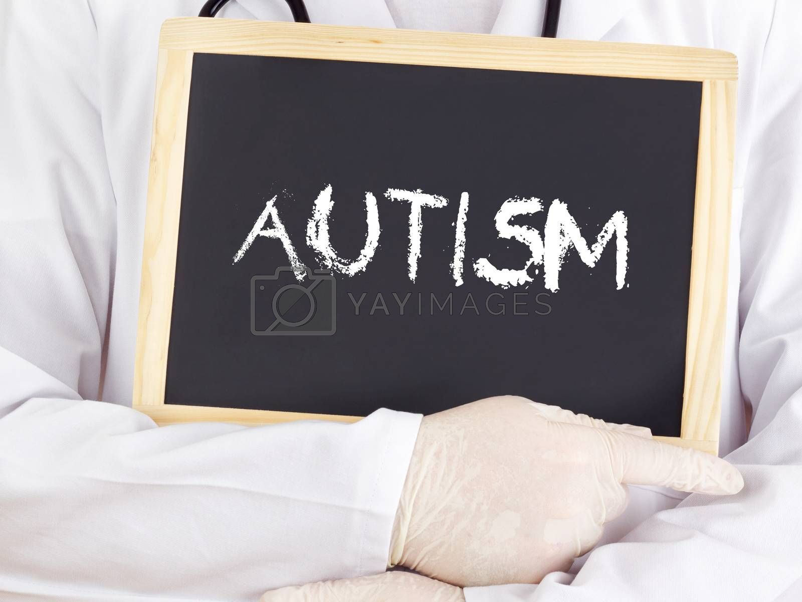 Royalty free image of Doctor shows information on blackboard: autism by gwolters