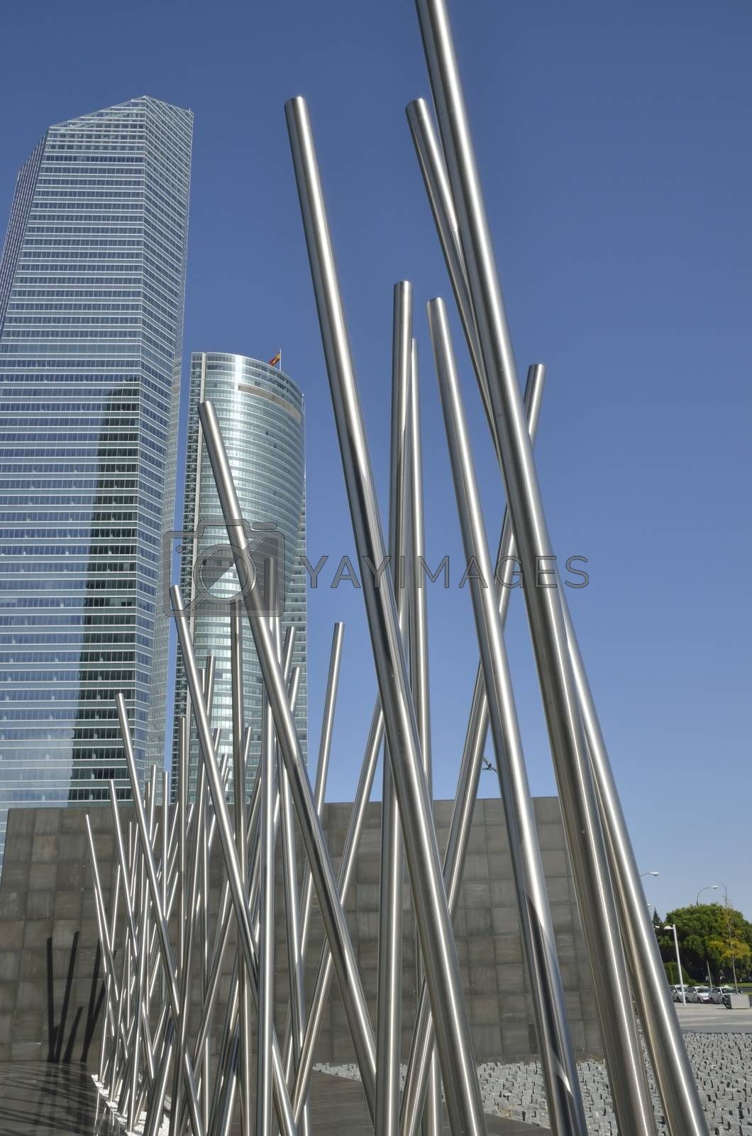 Steel sculpture in front of the Crystal and the Space Towers in the Four Towers Business Area, Madrid, Spain.   The Crystal tower was designed by Pelli and the  SpaceTower by  by Henry N. Cobb