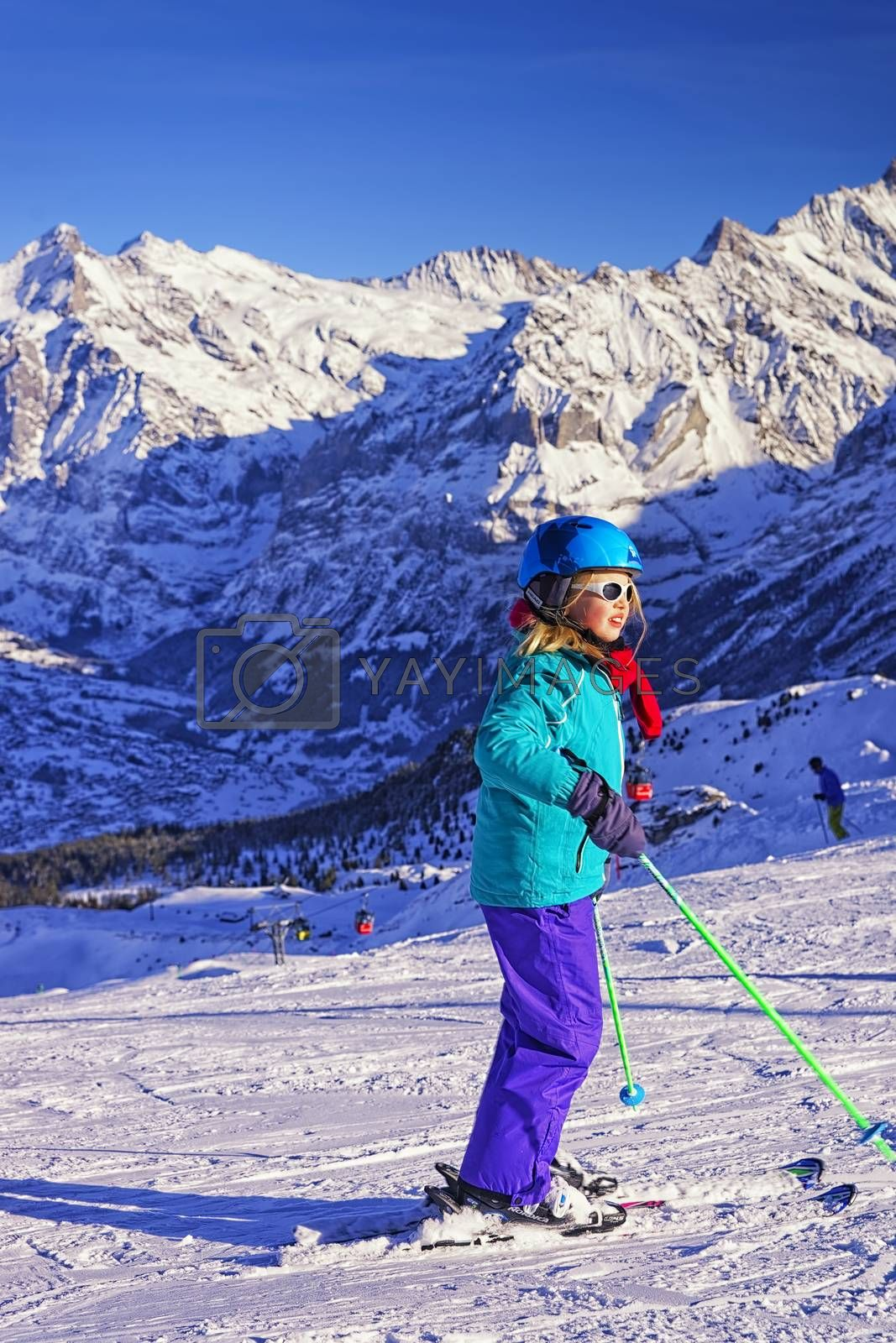 Royalty free image of Young blond girl on ski at winter sport resort in swiss alps by erix200511@mail.ru