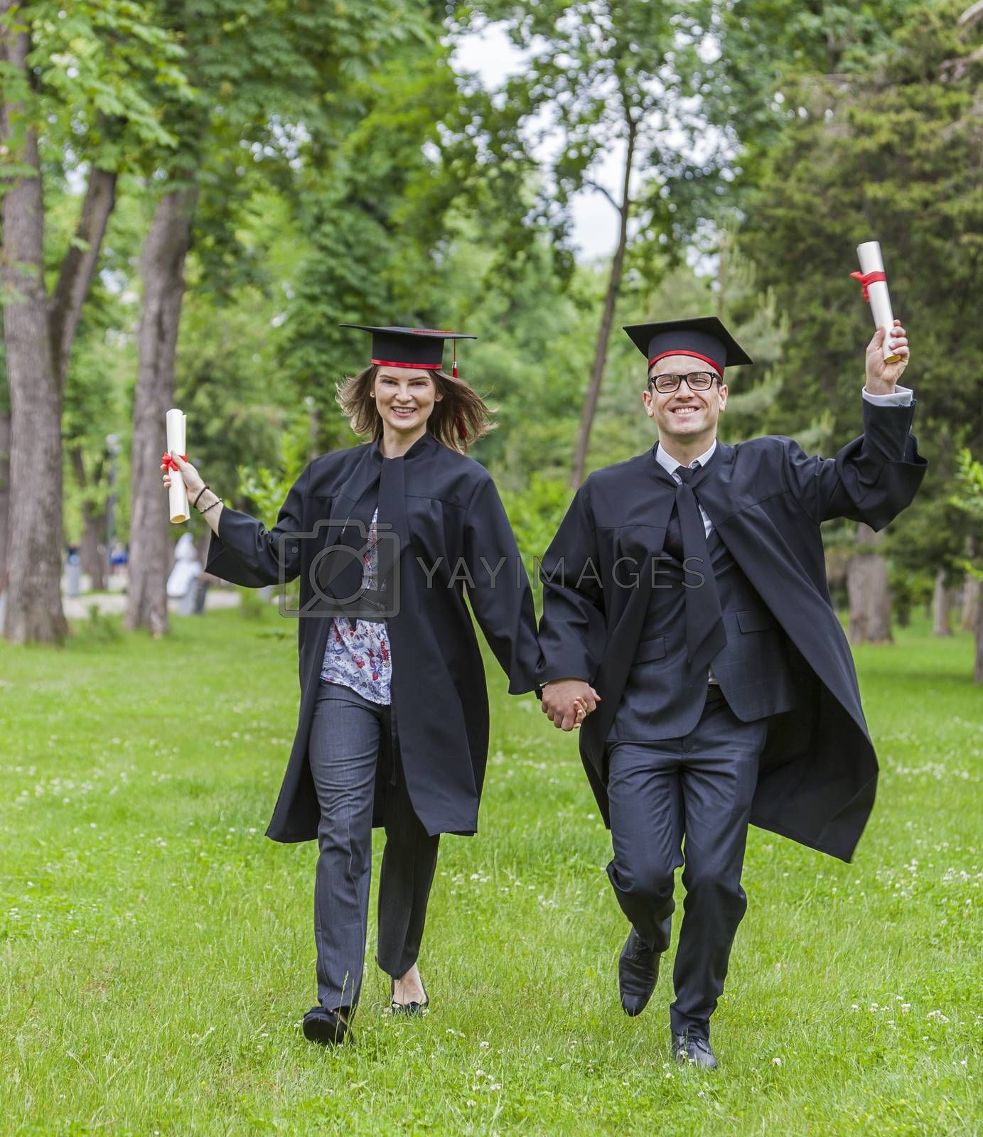 Young happy couple running in a green park in the graduation day.