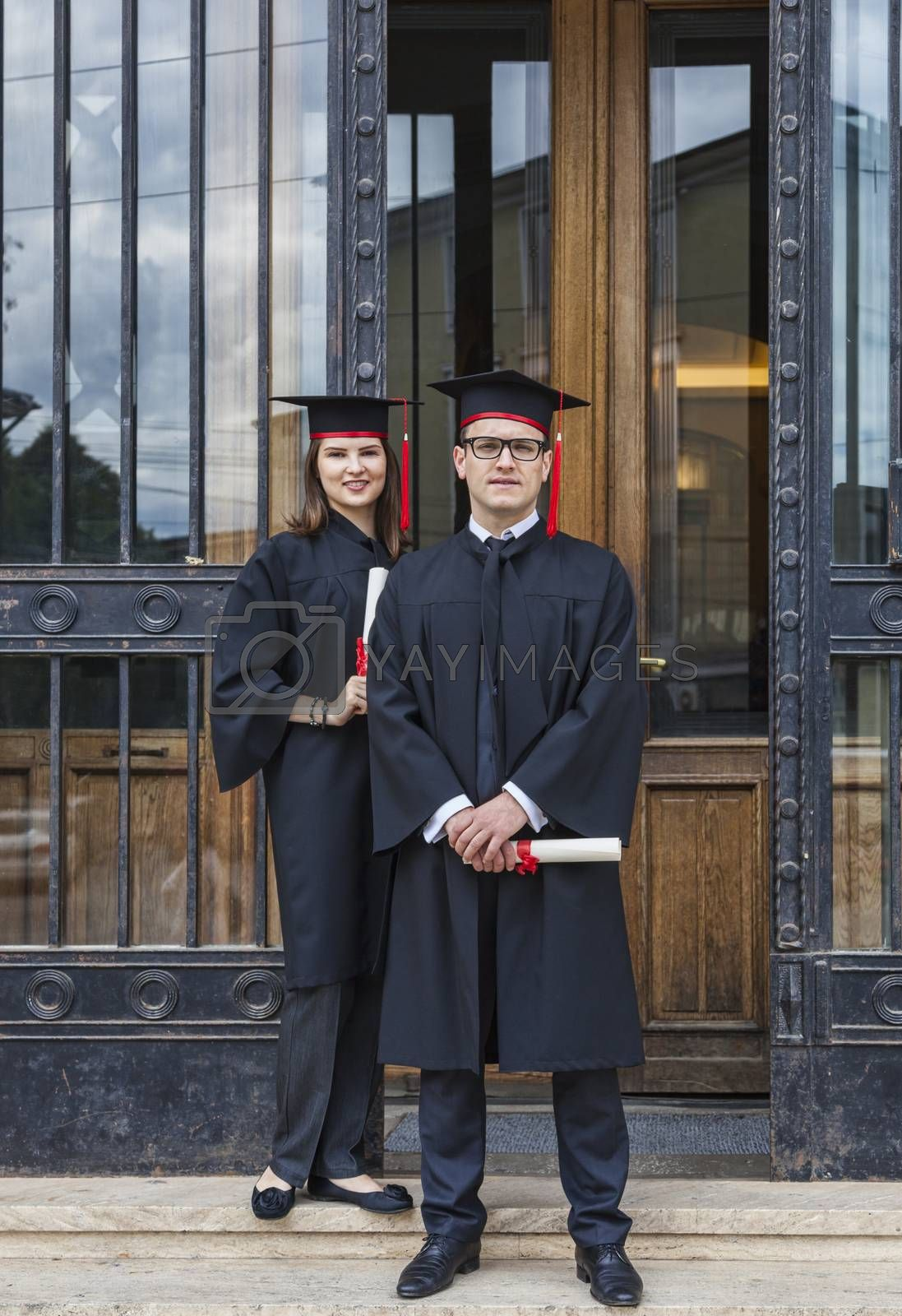 Young couple in the graduation day posing in front of the gate of the University.