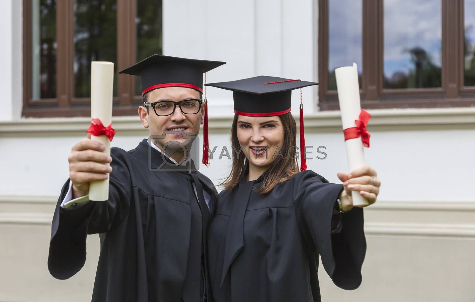 Happy couple in the graduation day proudly holding their certificates in front of the University wall.