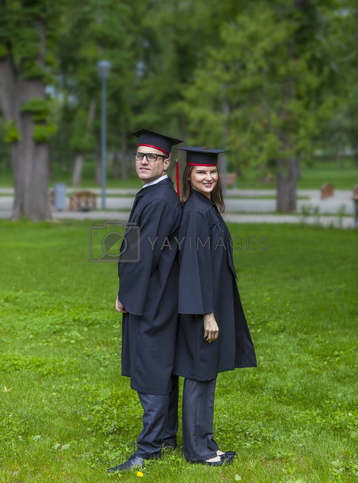 Young couple of students in the graduation day standing back in back in a park.